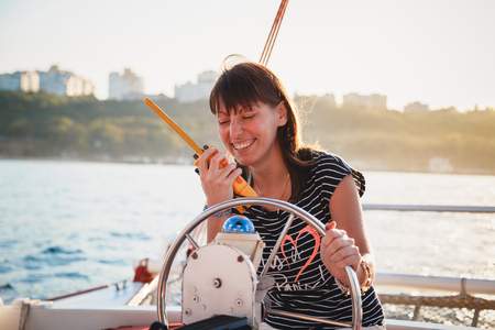 Young pretty smiling girl in striped shirt and white shorts driving luxury yacht and using walkie-talkie, hot summer day, sunset