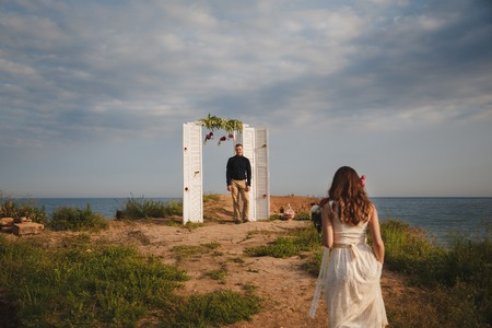 fiancee: Outdoor beach wedding ceremony, stylish happy groom is standing near wedding arch on the sea shore waiting for the bride.