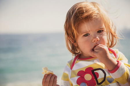 Close up of small beautiful girl eating bread with serious face outside at the beach.