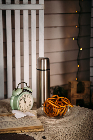 Old clock, thermos with hot tea and bagels on the table. Winter concept.