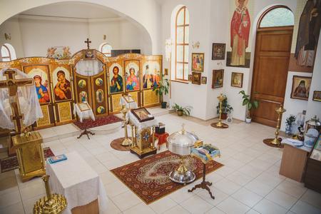 ODESSA, UKRAINE - MAY 1, 2015: Ukrainian Orthodox Christian Church. Preparing for christening in the church, church interior top view, golden religious utensils: bible, cross, baptismal font