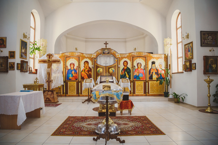ODESSA, UKRAINE - MAY 1, 2015: Ukrainian Orthodox Christian Church. Preparing for christening in the church, church interior view, golden religious utensils: bible, cross, baptismal font.