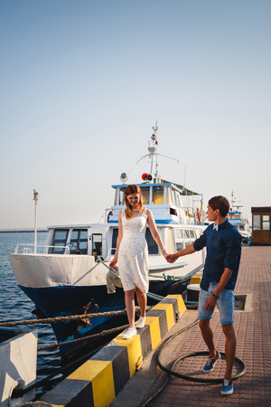 Cute young beautiful couple at pier at port with small yachts, hipster, happy smiling outdoor portrait.