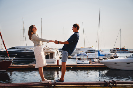Cute young beautiful couple at pier at port with small yachts, hipster, happy smiling outdoor portrait Reklamní fotografie
