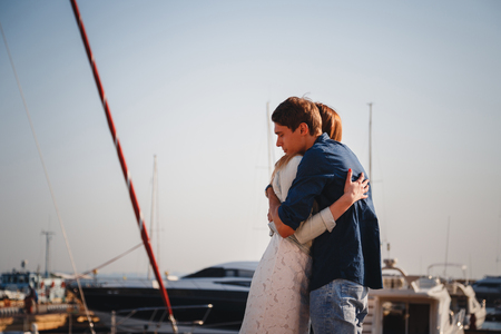 Cute young beautiful couple hugging at pier at port with small yachts, hipsters