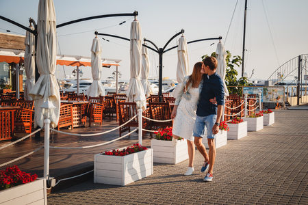 ODESSA, UKRAINE - AUGUST 06, 2015: Cute young beautiful couple kissing at pier at port with small yachts and summer cafe, happy smiling outdoor portrait.