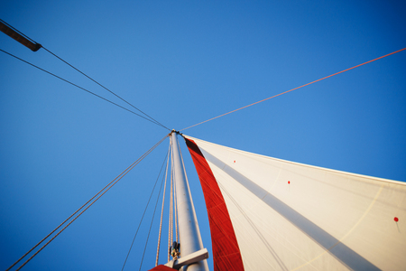 Top of the sailboat, mast head, sail and nautical rope yacht detail. Yachting, marine background. Reklamní fotografie