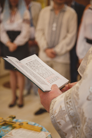 Christening in the church, priest is reading a prayer from the Bible. Details in the orthodox christian church.
