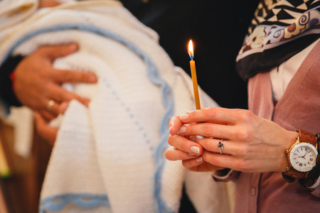 Christening in the church, woman is holdind candle, close up. Details in the orthodox christian church.