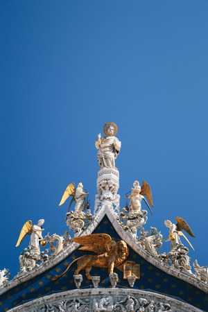 Close up of St Marks Apostle, angels and golden lion on the top of Basilica di San Marco, St Marks Basilica in Venice, Italy. Golden luxury detail of facade in summer against blue sky
