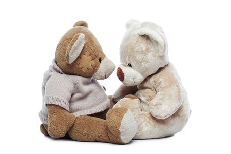 Two Teddy bears looking each other over white background photo