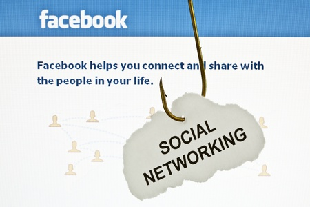 Rousse, Bulgaria - June 16, 2011: Close up of a hooked paper with printed 'SOCIAL NETWORKING' on it, infront of Facebook's main page. Facebook is the most popular social networking site in the world. Stock Photo - 9777346