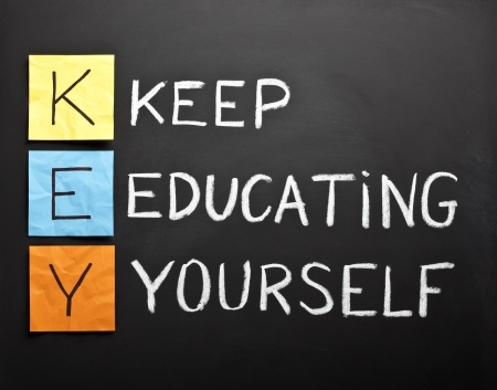 keep: KEY acronym - KEEP EDUCATING YOURSELF. Educational concept with different color sticky notes and white chalk handwriting on a blackboard.