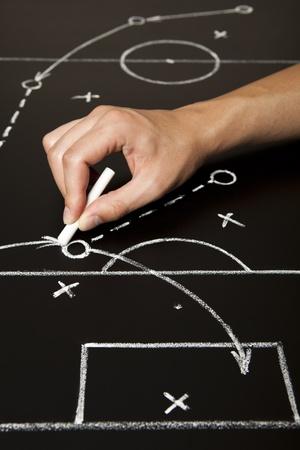 futbol soccer dibujos: Elaboraci�n de una estrategia de juego de f�tbol con tiza blanca en un pizarr�n de mano.