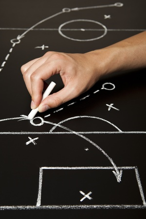 coach sport: Hand drawing a soccer game strategy with white chalk on a blackboard.