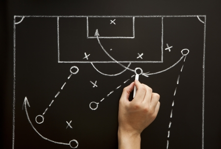 games hand: Man drawing a soccer game strategy with white chalk on a blackboard. Stock Photo