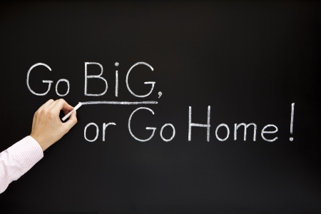 aspirations ideas: Hand writing GO BIG, OR GO HOME with white chalk on a blackboard. Stock Photo