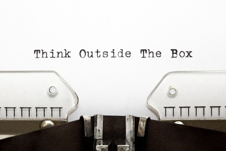 Concept image about unconventional or different thinking. THINK OUTSIDE THE BOX written on an old typewriter . photo