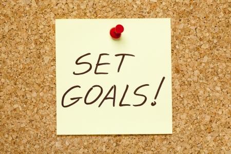 note of exclamation: Establezca metas! escrito en una nota adhesiva amarilla en un tablero de la oficina de anuncios de corcho.