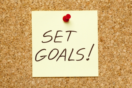 SET GOALS! written on an yellow sticky note on an office cork bulletin board. Stock Photo - 10895013