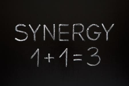 Concepto de sinergia 1 +1 = 3 hecho con tiza blanca sobre una pizarra.