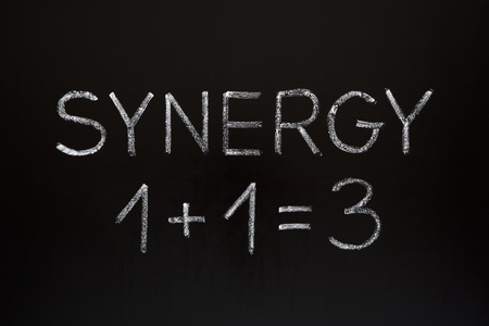 collaboration: Synergy concept 1+1=3 made with white chalk on a blackboard.  Stock Photo