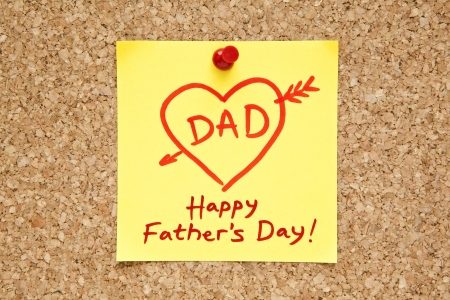 Sticky note with Happy Fathers Day on a cork bulletin board.  photo