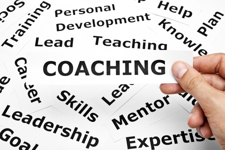 career development: Hand holding a piece of paper with Coaching written on it.  Stock Photo