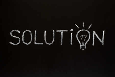 Solution concept with chalk drawn light bulb on the place of the letter O on blackboard. photo