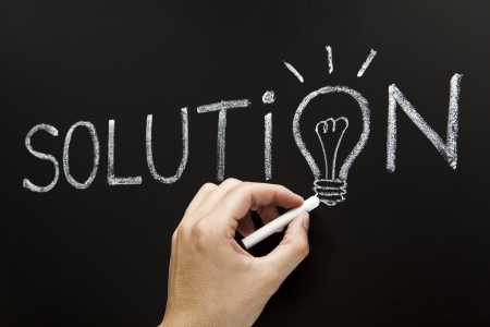 Hand showing chalk drawn light bulb on the place of the letter O in the word Solution on blackboard. Stock Photo - 14930286