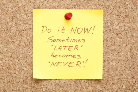 later: Do it Now, written on an yellow sticky note on a cork bulletin board
