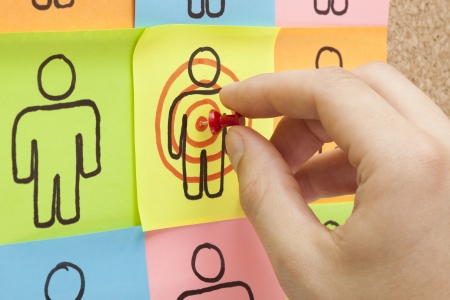 client service: Hand pinning a sticky note in the center of a customer target on cork board
