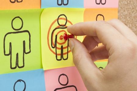 relation clients: Main �pinglant un pense-b�te dans le centre d'une cible client sur le panneau de li�ge Banque d'images