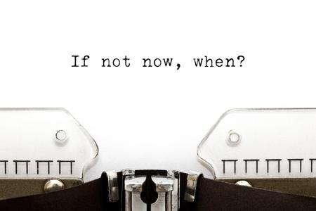 Concept beeld met Als niet nu, wanneer afgedrukt op een oude typemachine Stockfoto