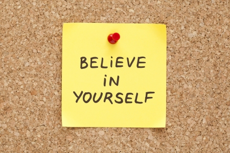 inspiration determination: Believe In Yourself, written on an yellow sticky note on a cork bulletin board Stock Photo