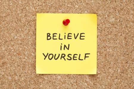 inspirerend: Geloof in jezelf, geschreven op een gele kleverige nota over een kurk prikbord