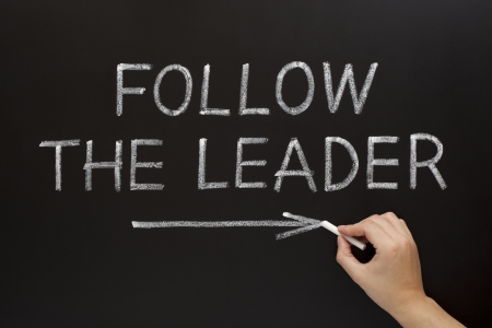 follower: Hand showing Follow The Leader written with white chalk on a blackboard