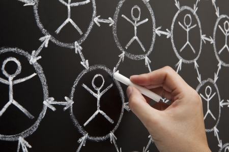 social relation: Hand showing social networking concept made with white chalk on a blackboard