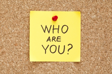 Who Are You written on an yellow sticky note pinned on a cork bulletin board.