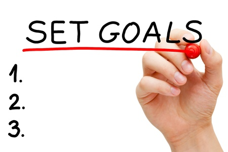 Hand underlining Set Goals with red marker isolated on white. Stock Photo