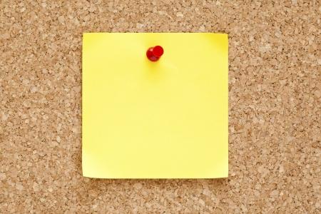 corcho: En blanco nota adhesiva amarilla se consumía en un tablero de corcho.