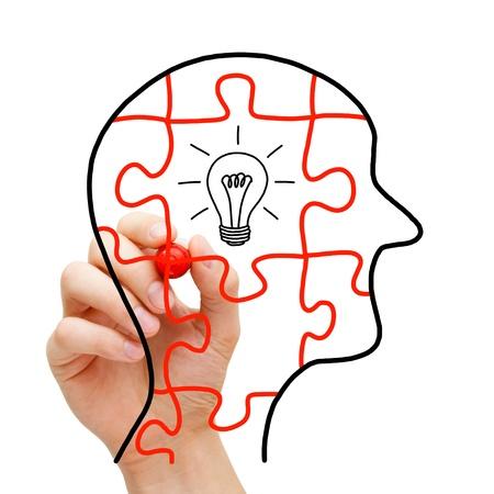 pensador: Concepto de pensamiento creativo. Puzzle cabeza humana con una bombilla incandescente de luz en el centro.
