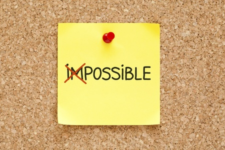 unachievable: The word Impossible turning into Possible on yellow sticky note