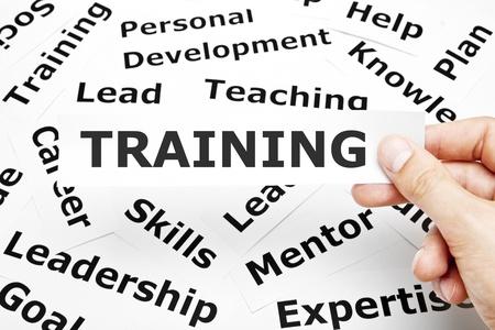 training: Hand met een stuk papier met Training op geschreven. Stockfoto