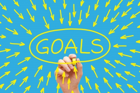 Hand drawing Goals concept with yellow marker on transparent wipe board on blue background.