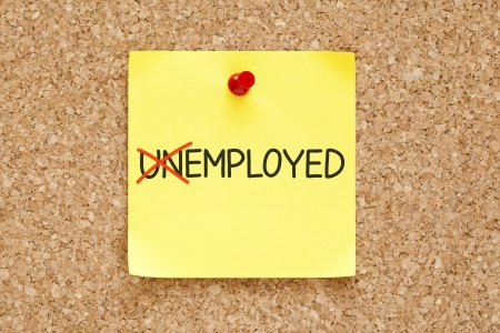 in need of space: Turning the word Unemployed into Employed with red marker on yellow sticky note pinned with red push pin. Stock Photo