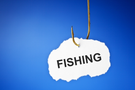 Fishing printed on white piece of paper hanging on a fishing hook over blue background. Hooked on fishing concept. photo