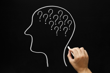 reasoning: Hand drawing Human head and many question marks with white chalk on blackboard. Stock Photo