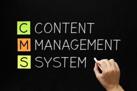 cms: Hand writing Content Management System with white chalk on blackboard. Stock Photo