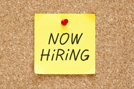 Now Hiring written on an yellow sticky note pinned with red push pin on cork bulletin board. Stock Photo - 17668109